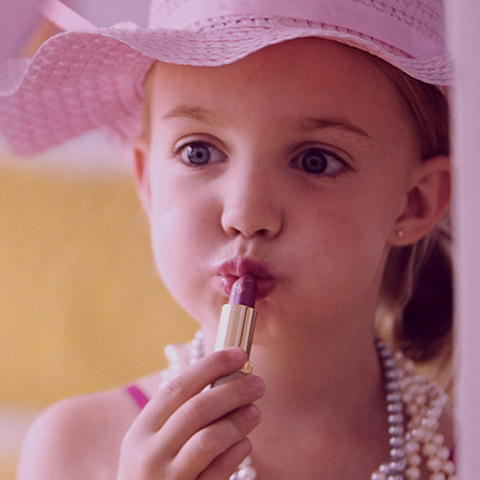 Little girl putting on lipstick