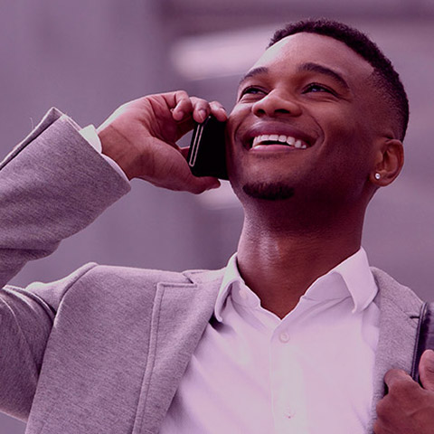 Happy young man talking on mobile phone inside building
